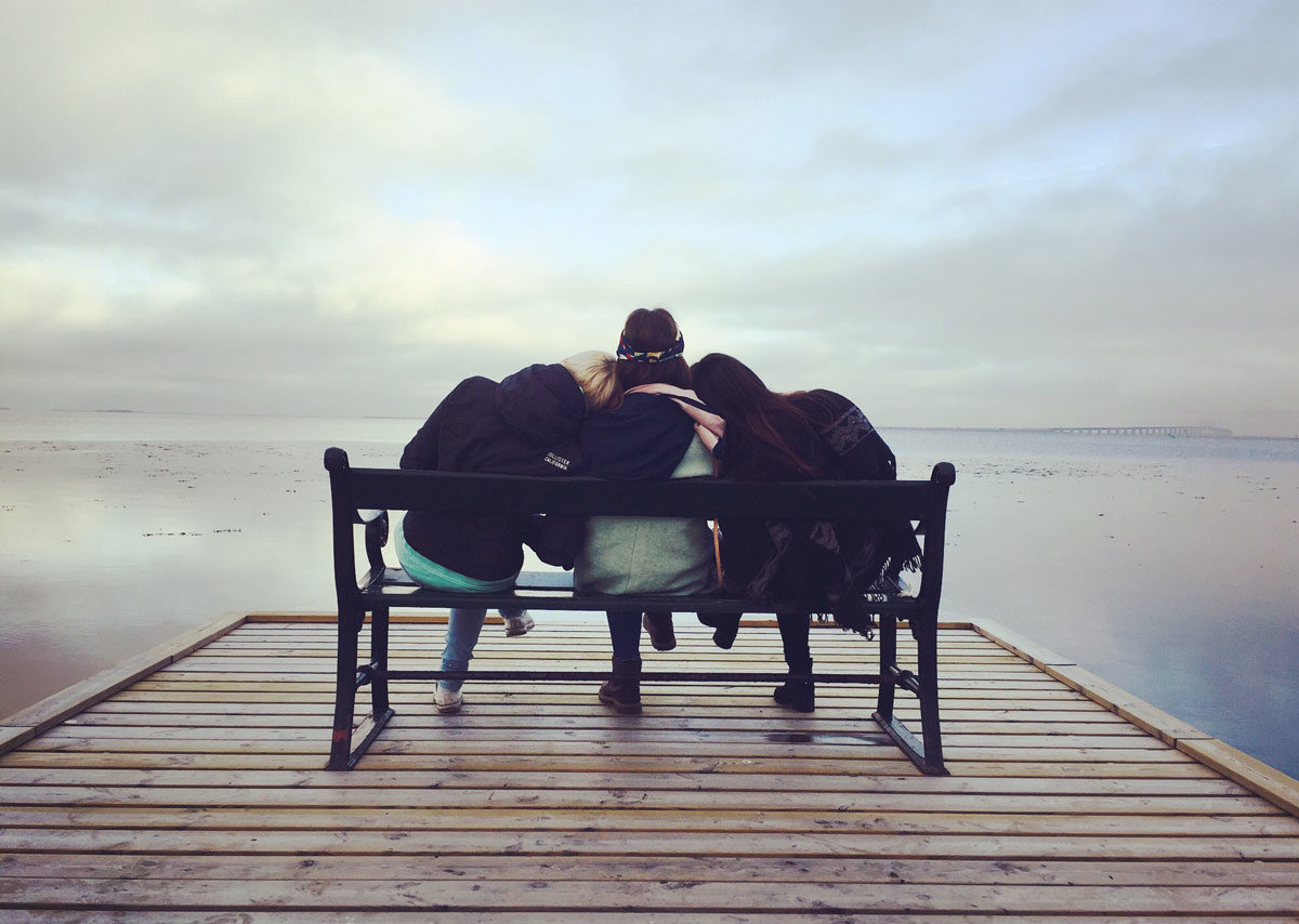 Three friends sitting on a bench on a wooden dock