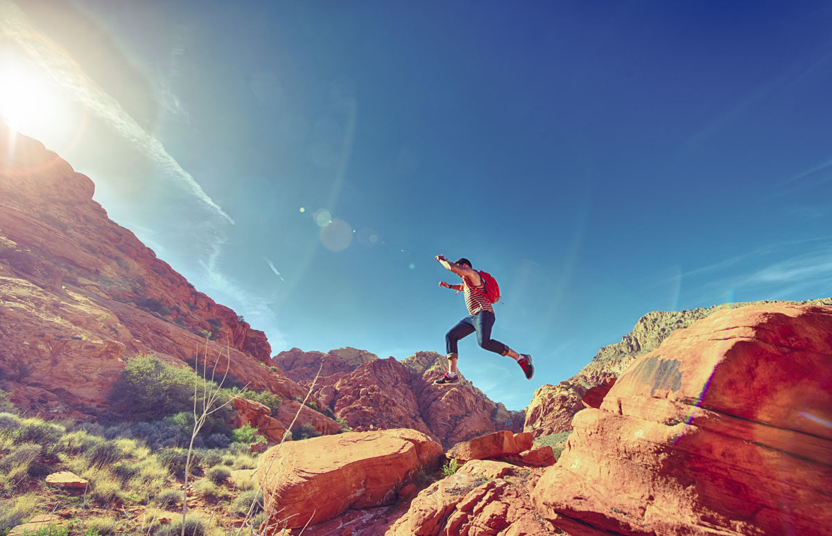 Hiker leaping from boulder to boulder in desert canyon