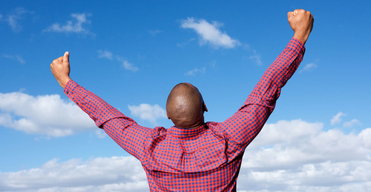 Man reaching skywards triumphantly into a blue sky