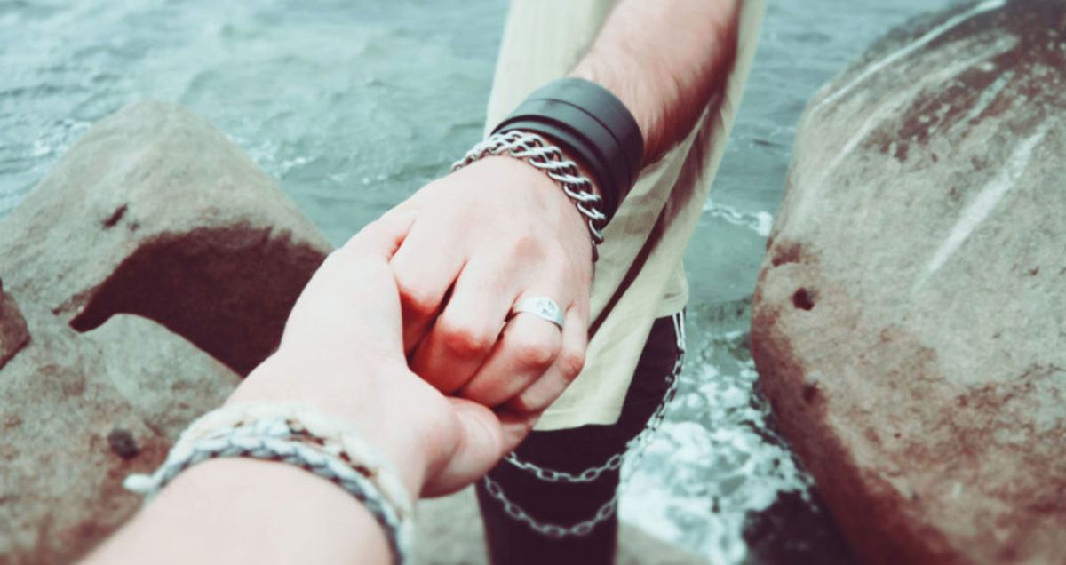 close up of hands with punk-inspired accessories standing on rocks of a shoreline