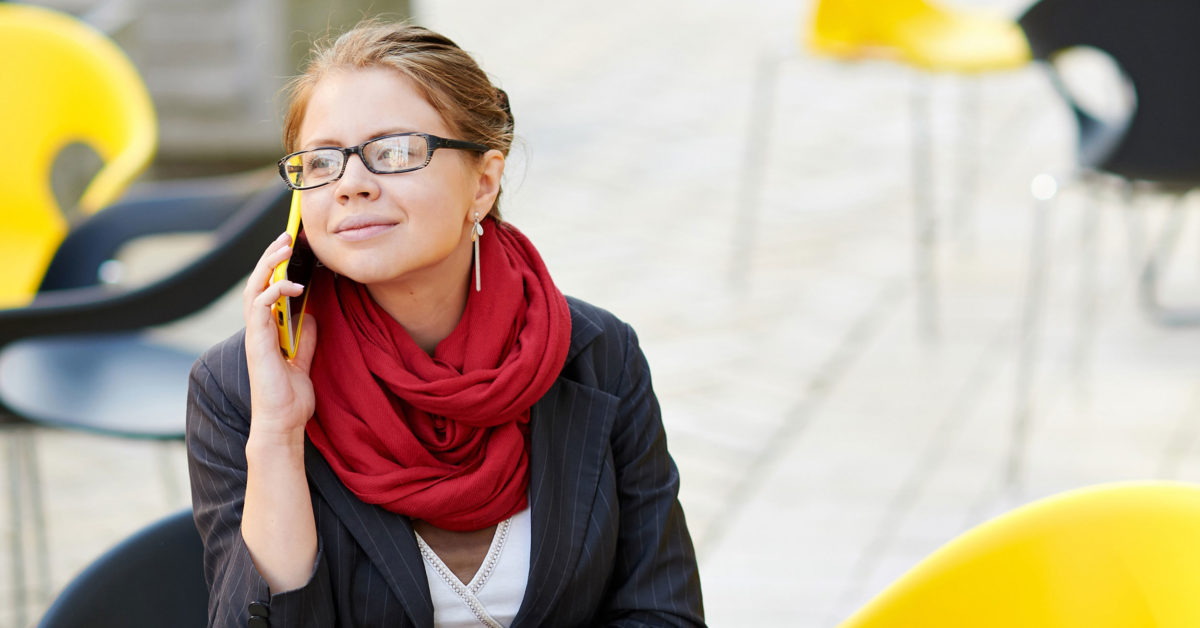 Woman sitting at modern table outside with red scarf, glasses and holding a cell phone