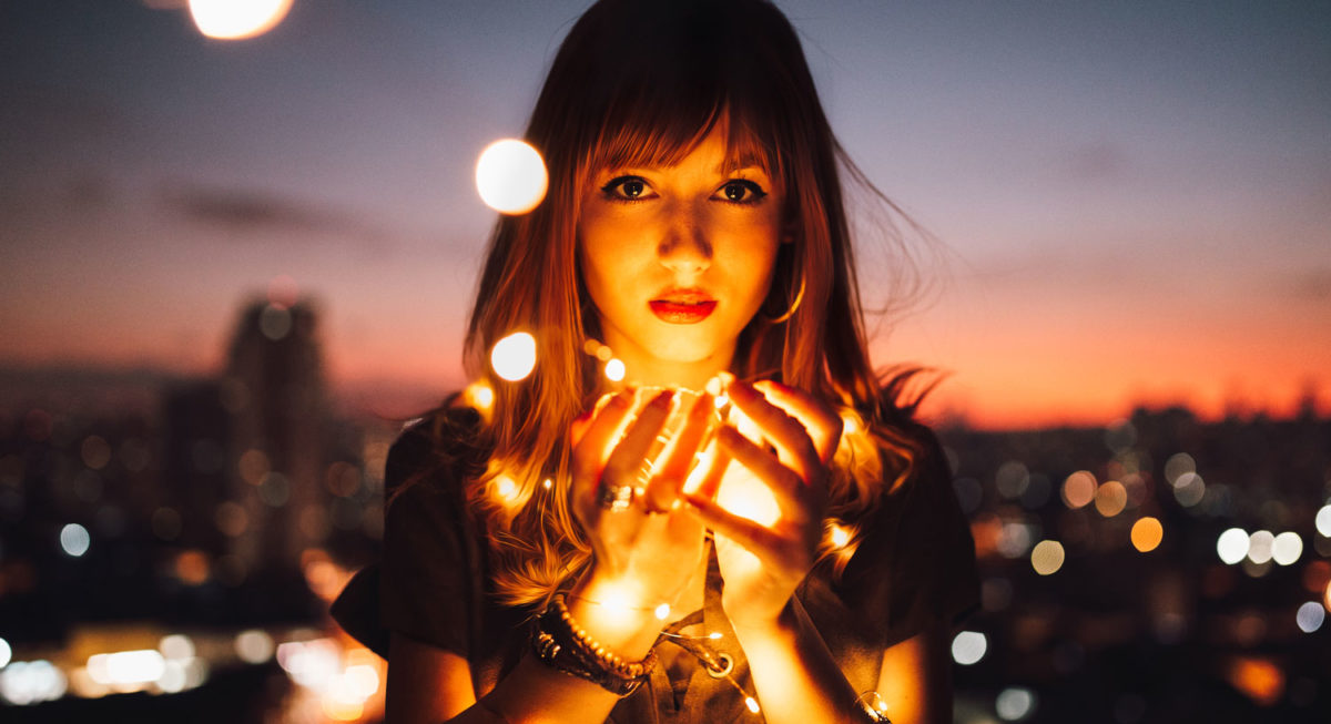 Woman holding fairie lights with a background of a city skyline at sunset