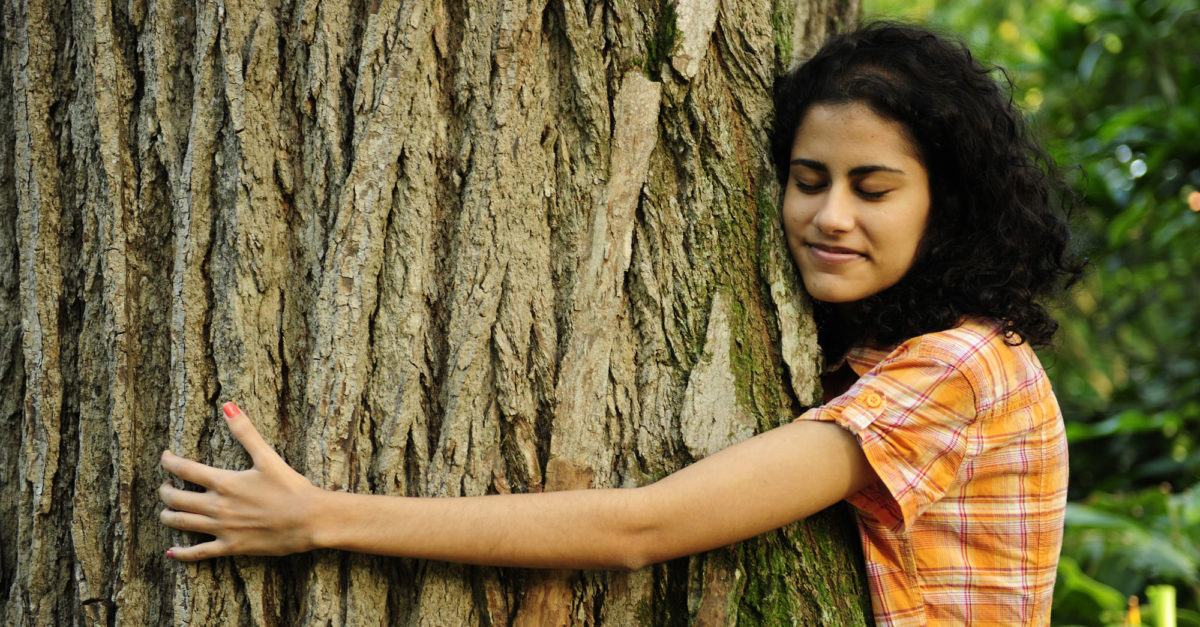 Woman hugging a huge tree with eyes closed