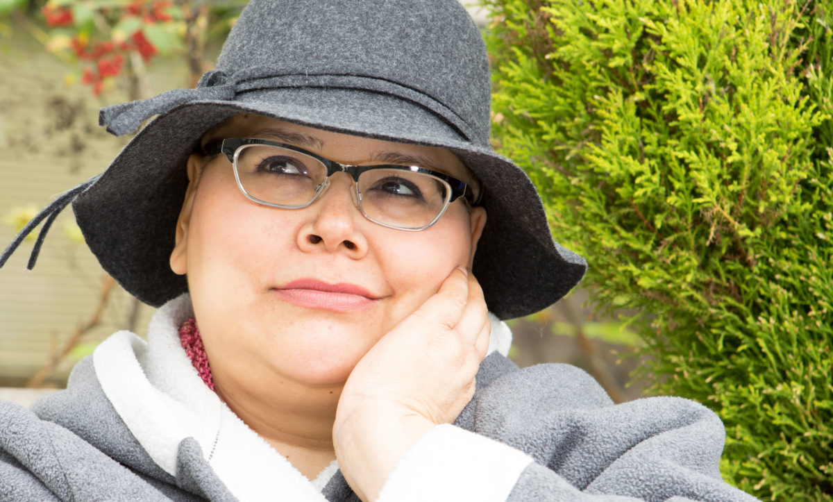 Woman in hat with glasses sitting outside deep in hopeful thought