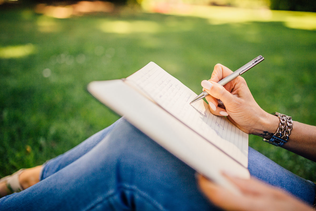 Woman writing in journal outside in the grass